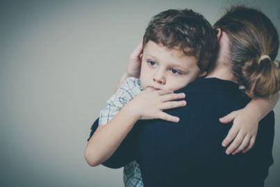 bambino triste abbraccia la madre