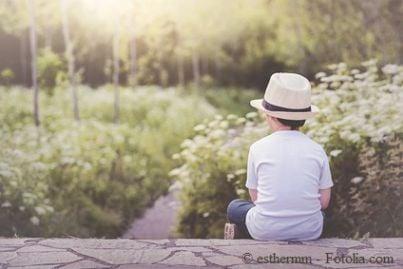 Bambino seduto di spalle che guarda la natura