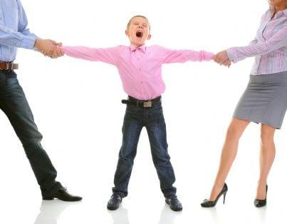 bambino conteso dai genitori che lo tirano per le braccia
