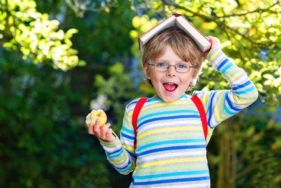 bambino a scuola con zaino in spalla e libro in testa