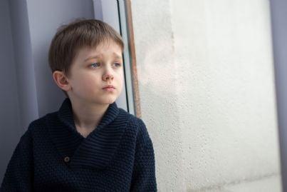 bambino solo dietro una finestra