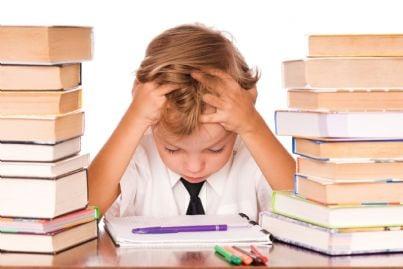 bambino triste che fa compiti a casa