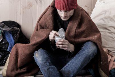 giovane uomo barbone che mangia per strada