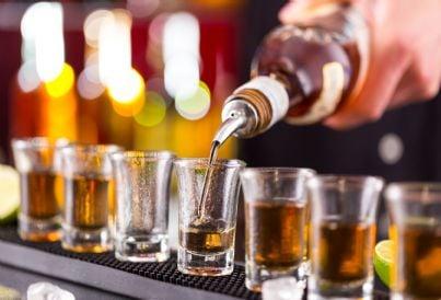 barman versa da bere nelle bottiglie