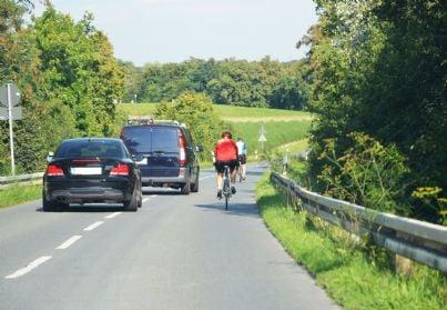 auto che sorpassano ciclisti in bicicletta
