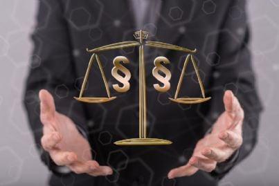 mani di uomo verso bilancia della giustizia