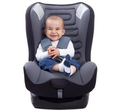 bimbo che ride seduto in seggiolino per auto