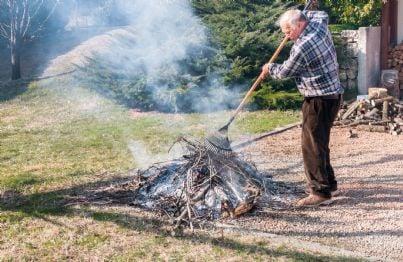 uomo che brucia rami in giardino