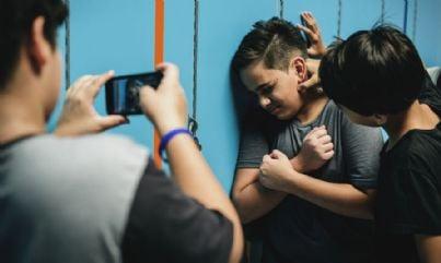 ragazzi che fanno bullismo in corridoio e filmano con cellulare