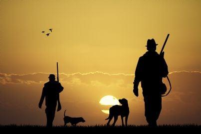 cacciatori con cane al tramonto