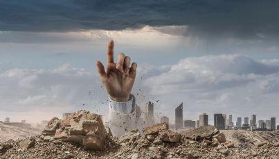 mano di uomo caduto sotto macerie che chiede aiuto