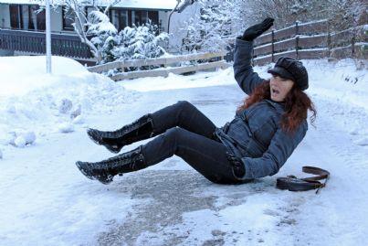 donna che cade sulla strada ghiacciata