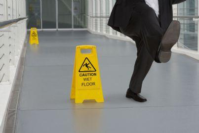 uomo che cade su pavimento bagnato