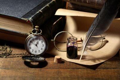Scrivania con calamaio libri e orologio