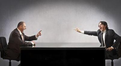 uomini che si calunniano e litigano seduti ad un tavolo