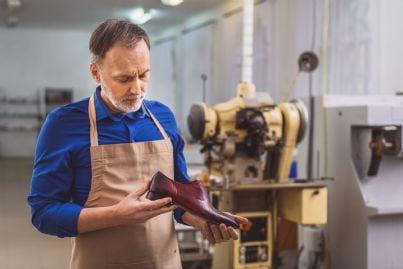 un calzolaio che esamina una scarpa