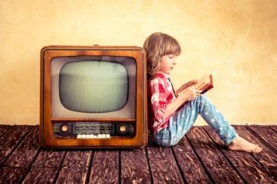 bambina che legge appoggiata a vecchia tv