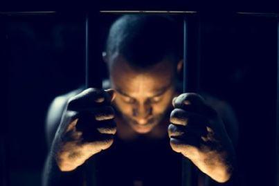 uomo tra le sbarre del carcere
