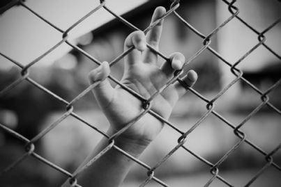 mano di ragazzo attaccato a rete carcere minorile