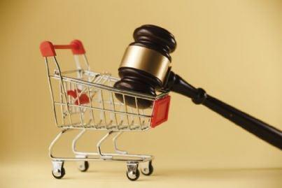 carrello della spesa con martello per tutela diritti