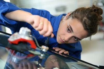 Ragazza che sta riparando un'autovettura