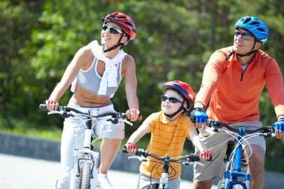 famiglia va in bici indossando il casco
