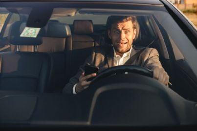 uomo usa cellulare alla guida