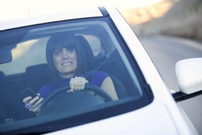 donna alla guida con cellulare in mano