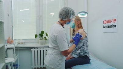 infermiera fa vaccino covid in un centro