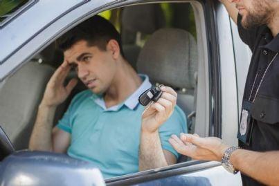 uomo consegna chiavi auto alla polizia