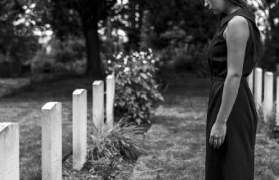 donna triste al cimitero davanti a una tomba