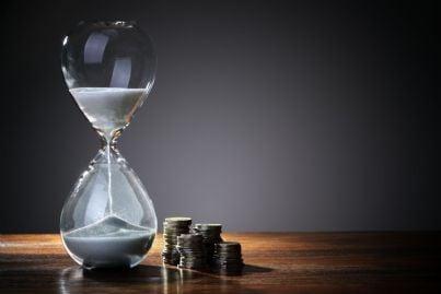 clessidra che segna il tempo con soldi a fianco