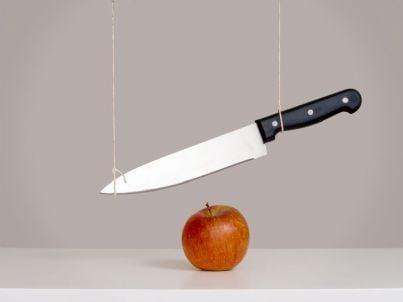 coltello pende su una mela concetto di spada di Damocle
