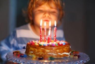 bambino che spegne le candeline sulla torta di compleanno