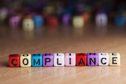 parola compliance scritta coi dadi sul tavolo