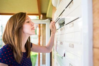 donna controlla la propria cassetta della posta
