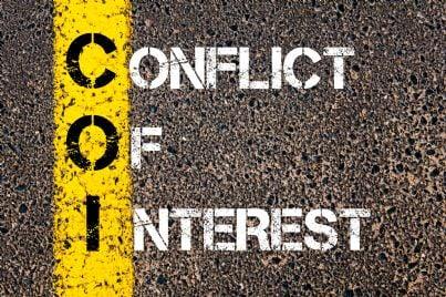 parole conflitto di interessi scritte su asfalto