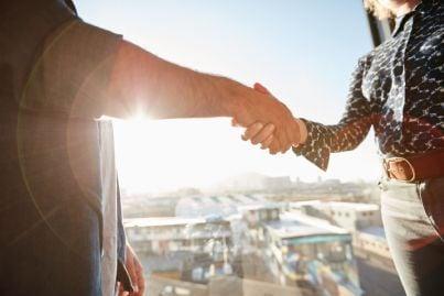uomo e donna si stringono le mani dopo aver stretto accordo