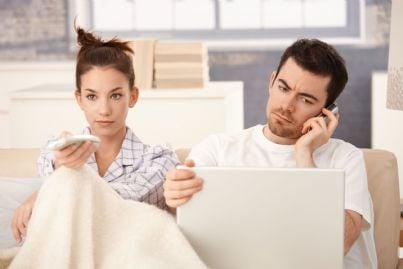 coppia che guarda la tv lei annoiata lui telefona per disdetta