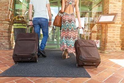 coppia di turisti con valigie che si appresta ad entrare in hotel