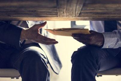 mani che passano busta con soldi sotto il tavolo