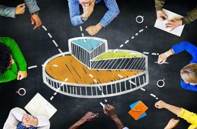 uomini intorno a un tavolo con grafico a torta su crescita