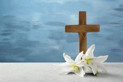 croce religiosa di legno e giglio su un tavolo