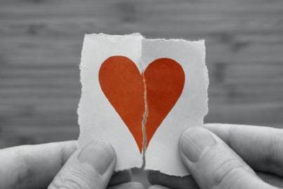 uomo tiene cuore spezzato di carta in mano