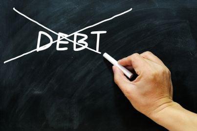 mano che cancella la parola debito