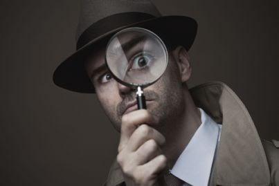 uomo con lente vestito da detective