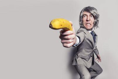 Uomo con in mano una banana puntata a modo di pistola