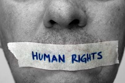 uomo con cerotto sulla bocca con scritto diritti umani