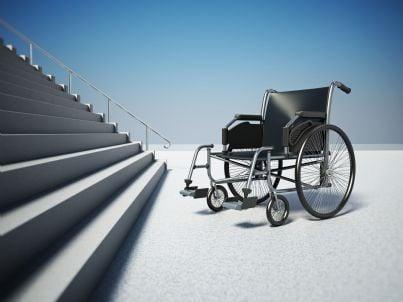 sedia a rotelle ferma di fronte a scale