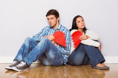 coniugi in crisi seduti con cuore spezzato in mano